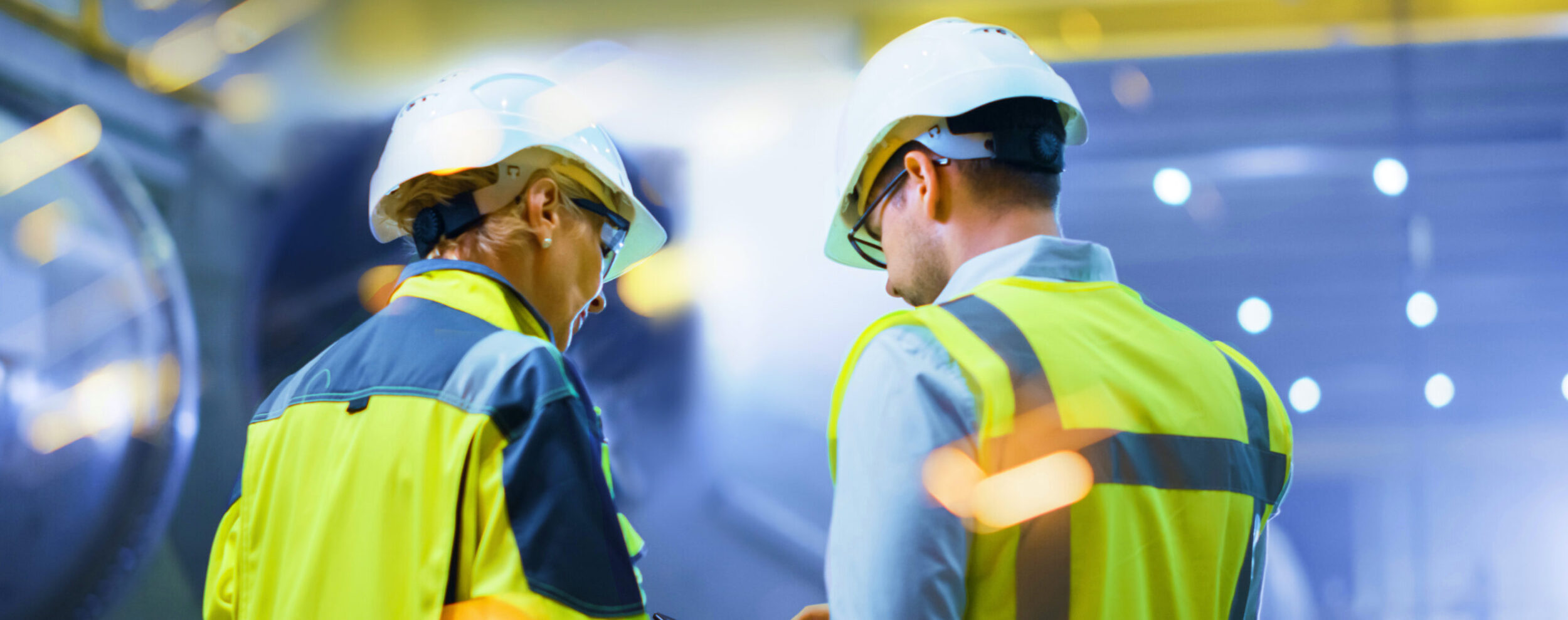 Man and woman in high-vis jackets and hard hats working at a facility