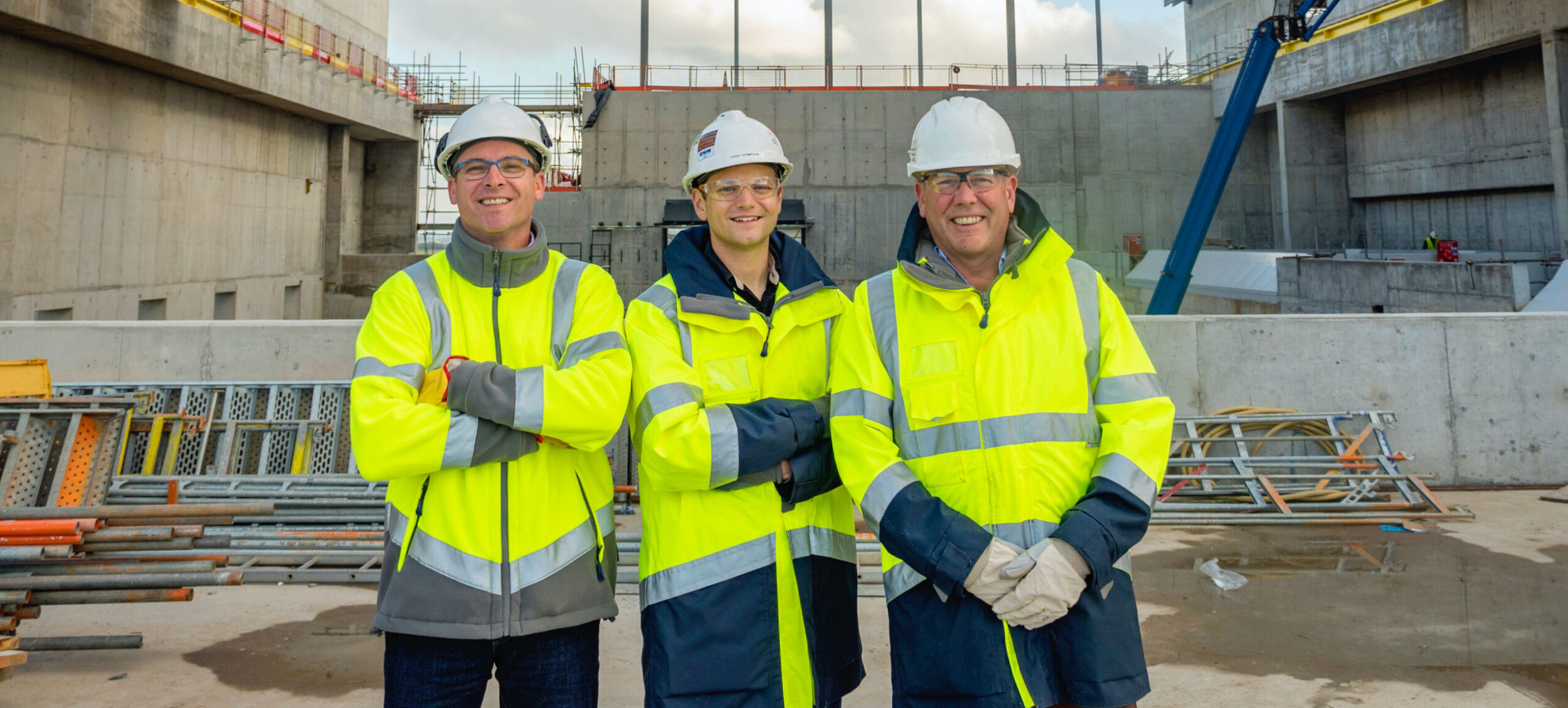 enfinium employees wearing high-vis jackets and hard hats outside a facility